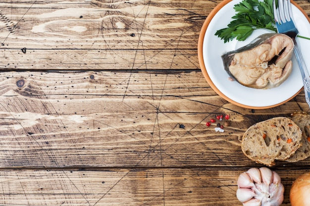 Ingredienti per la zuppa di salmone, pezzi di pane, cipolla e aglio con verdure sul tavolo di legno.