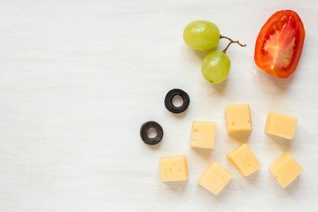 Ingredienti per snack, formaggio con olive e pomodoro su un tavolo bianco