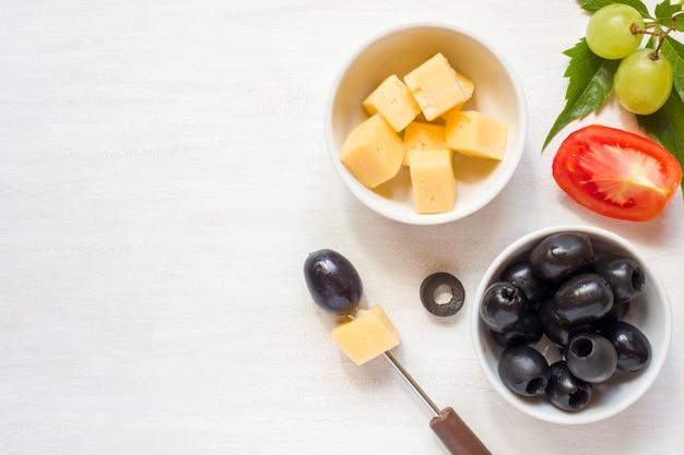 Ingredienti per snack, formaggio con olive e pomodoro, uva su un tavolo bianco