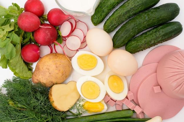 Ingredienti per una ricetta di zuppa okroshka fredda nazionale russa fatta in casa su una luce.