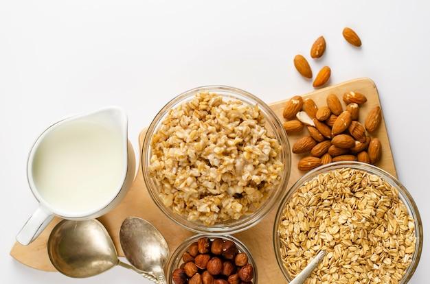 Ingredienti per una sana colazione - fiocchi d'avena, latte e mandorle su bianco