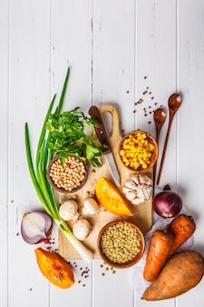 Ingredienti per zuppa di verdure vegano con lenticchie, funghi e ceci su sfondo bianco.