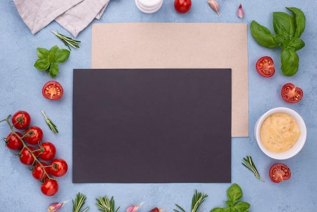 Ingredienti piatti laici e foglio di carta bianco