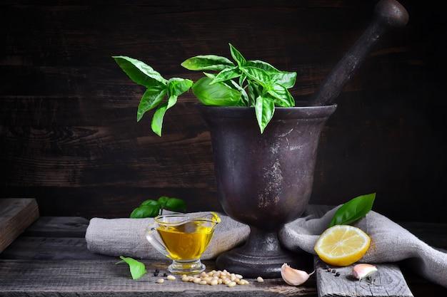 Ingredienti ricetta italiana per pesto di basilico su uno sfondo scuro,