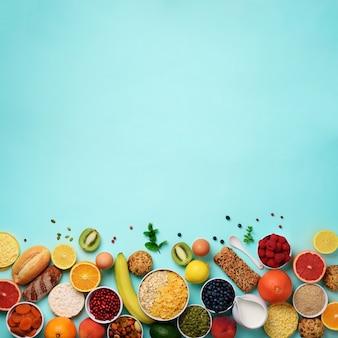 Ingredienti sana colazione, cornice di cibo. avena e fiocchi di mais, uova, noci, frutta, bacche, pane tostato, latte, yogurt, arancia, banana, pesca