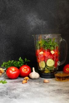Ingredienti tradizionali di zuppa fredda di zuppa di pomodoro estiva in un frullatore. pomodori, pepe, aglio, basilico, prezzemolo, olio d'oliva e crostini. cucina mediterranea, spagnola. sfondo nero. copia spazio