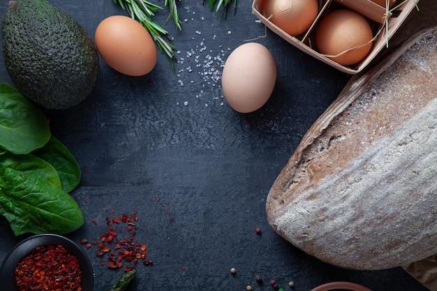 Ingridienti per cucinare. verdure fresche e biologiche, pane senza glutine, uova ecologiche e prezzemolo. verdure di primavera sul muro di pietra scura con spazio di copia. disteso. concetto di cibo sano