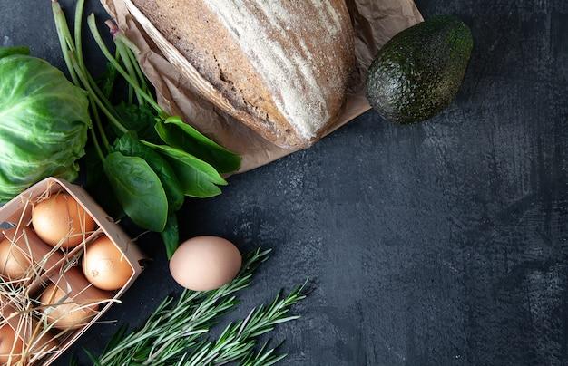 Ingridienti per cucinare. verdure fresche e organiche, pane senza glutine, uova ecologiche e prezzemolo. verdure di primavera, avocado su sfondo di pietra scura con spazio di copia. disteso. concetto di cibo sano