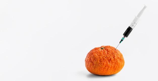 Iniezione di sostanze chimiche in un'arancia con la siringa