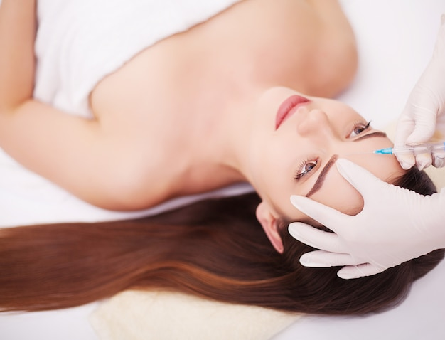 Iniezione e bellezza donna viso. ragazza attraente con una pelle perfetta.