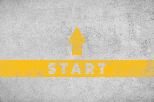 Inizia il concetto. pavimento in cemento invecchiato con freccia e testo dipinti di giallo