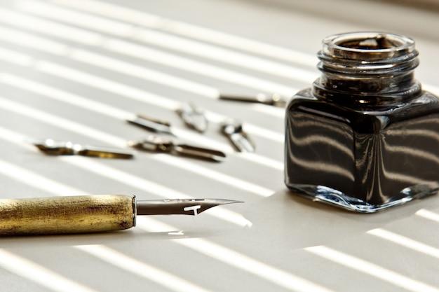 Inkpot con punte di metallo per la penna su uno sfondo bianco nei raggi solari.