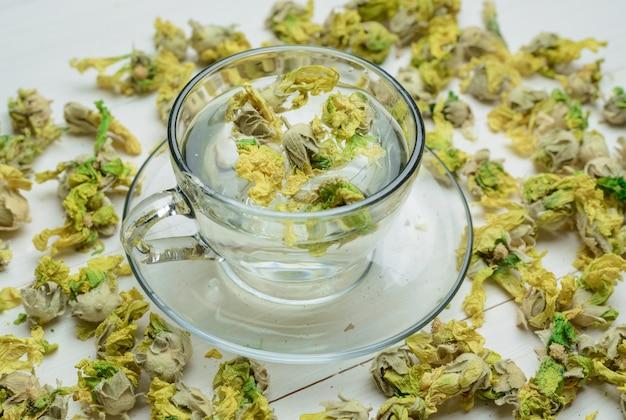 Innaffi con le erbe secche in una tazza sulla tavola di legno, vista dell'angolo alto.