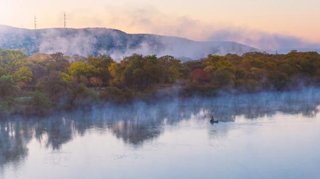 Innaffi l'evapoation sul fiume all'alba e il pescatore solo su una barca alla stagione di autunno
