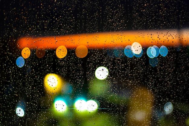 Innaffi la goccia alle finestre e al bokeh della città nel tramonto