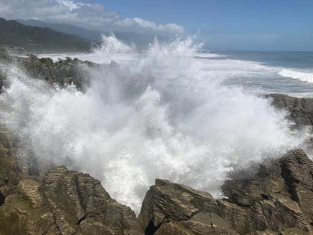 Innaffi la spruzzata attraverso uno sfiatatoio alla costa ovest della nuova zelanda della roccia dei pancake.