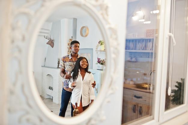 Innamorati afroamericani delle coppie che bevono vino in cucina al loro appuntamento romantico.