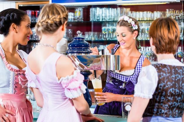 Innkeeper in pub bavarese con i clienti