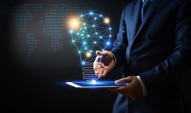 Innovazione e tecnologia, compressa della tenuta della tenuta dell'uomo d'affari con la lampadina creativa e linea di collegamento