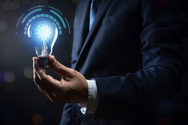 Innovazione ed energia del pensiero creativo, uomo d'affari che tiene lampadina che emette luce e illuminazione con collegamento