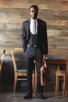 Inquadratura a figura intera di imprenditore africano di successo in abbigliamento formale, con valigetta