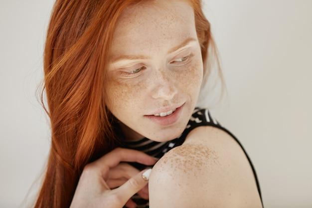 Inquadratura altamente dettagliata di una tenera e carina ragazza adolescente con un timido sorriso debole, capelli sciolti rossi e una pelle sana e pulita guardando sopra la spalla