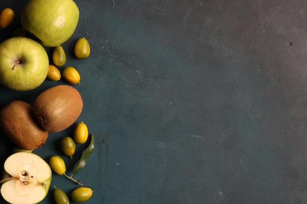 Inquadratura con mele verdi, kiwi e kinkan su sfondo grigio