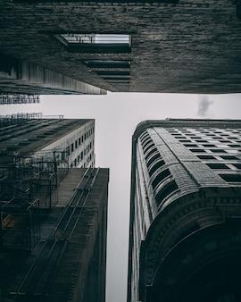Inquadratura dal basso degli edifici alti con scale di metallo in una giornata uggiosa