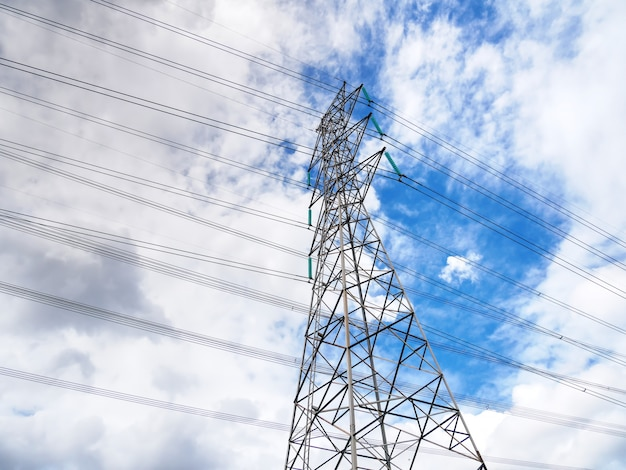 Inquadratura dal basso della struttura della torre di alta tensione e linee elettriche contro il cielo nuvoloso blu