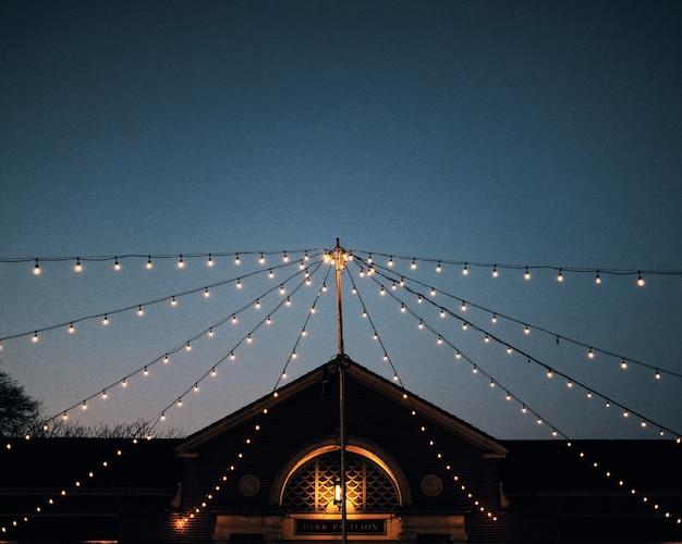 Inquadratura dal basso di stringhe di lampadine attaccate a un palo davanti a un padiglione del parco al crepuscolo