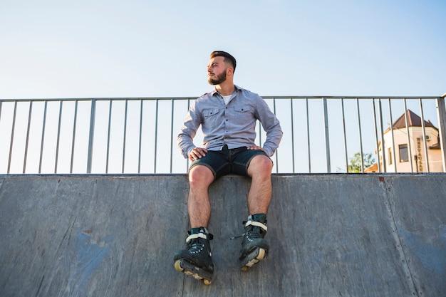 Inquadratura dal basso di un giovane maschio rollerskater