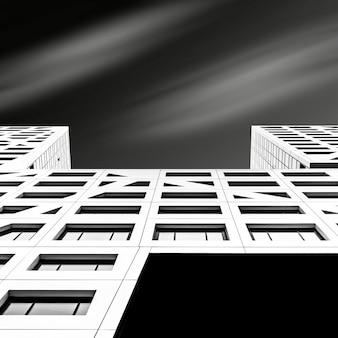 Inquadratura dal basso di un grattacielo bianco sotto un cielo scuro