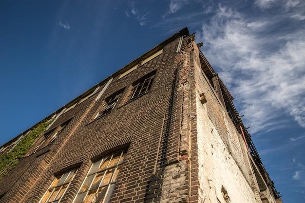Inquadratura dal basso di un vecchio edificio in pietra sotto il cielo con poche nuvole