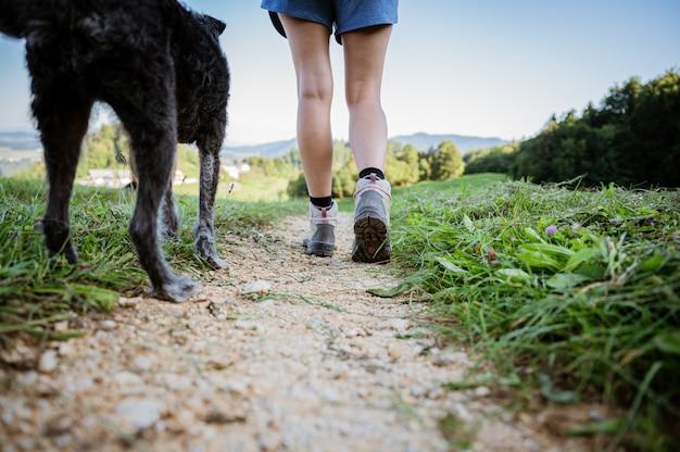 Inquadratura dal basso di una donna in scarpe da trekking sul sentiero