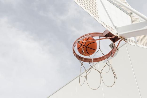 Inquadratura dal basso di una pallacanestro che cade attraverso il cerchio