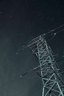 Inquadratura dal basso di una torre di trasmissione sotto un cielo stellato