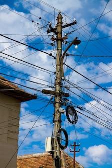 Inquadratura dal basso verticale di molti cavi elettrici sotto un cielo nuvoloso