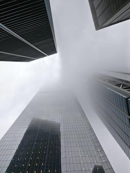 Inquadratura dal basso verticale di un palazzone avvolto nella nebbia