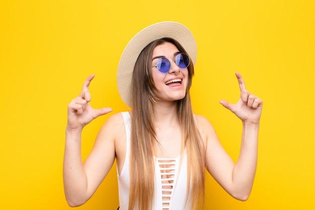 Inquadratura della giovane donna graziosa o delineare il proprio sorriso con entrambe le mani, sembrante positivo e felice, concetto di benessere