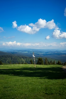 Inquadratura di un cartello contro un paesaggio di alberi e colline