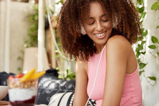 Inquadratura laterale di una donna dall'aspetto piacevole con acconciatura afro, ascolta la traccia audio in cuffia, guarda felicemente in basso, ha un buon riposo, gode di un'atmosfera tranquilla a casa. persone e concetto di svago