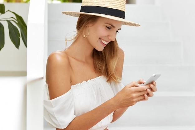 Inquadratura laterale di una giovane turista felice che si diverte a chattare online sul moderno dispositivo smart phone, condivide impressioni come ha un viaggio emozionante, indossa cappello di paglia e camicetta bianca con le spalle nude.