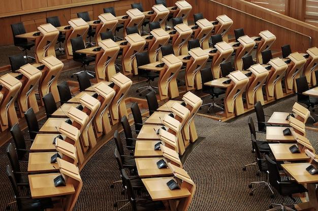 Inquadratura orizzontale delle scrivanie all'interno dell'edificio del parlamento scozzese