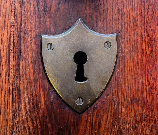 Inquadratura ravvicinata di un buco della serratura graffiato su una porta di legno