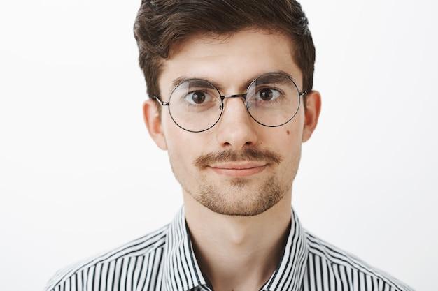 Inquadratura ravvicinata di un ragazzo creativo intelligente fiducioso con barba e baffi in occhiali rotondi, in piedi spensierato e sicuro di sé sul muro grigio, parlando casualmente o ascoltando un amico sul muro grigio