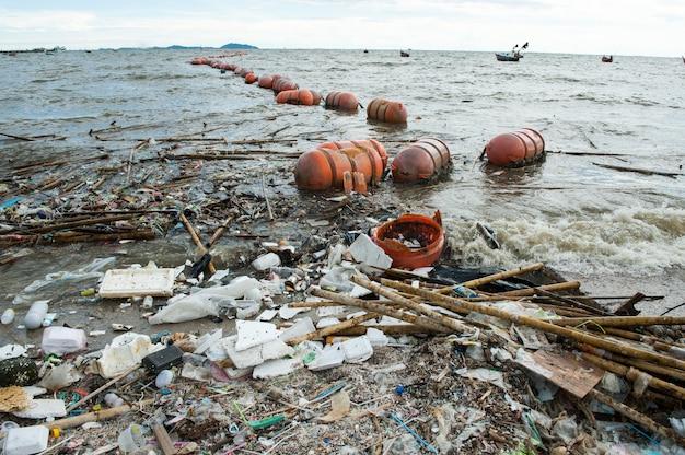 Inquinamento da spiaggia, schiuma, bambù, plastica e rifiuti dall'oceano sulla spiaggia