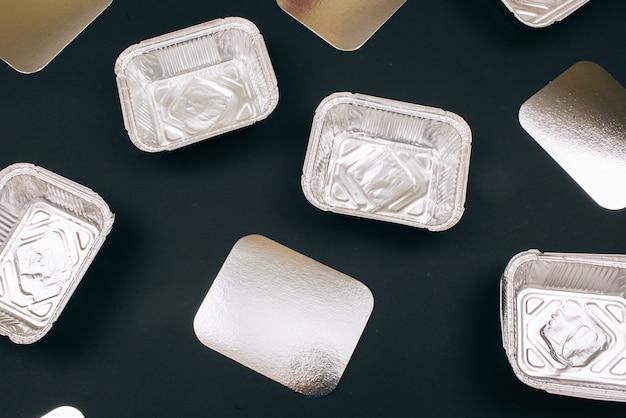 Inquinamento di plastica. contenitori di alluminio per alimenti e cartoni d'argento, vista dall'alto. plastica monouso. un problema ambientale, direttiva ue