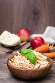 Insalata americana pronta dello slaw delle cole fatta da cavolo, da sedano, dalle carote e dalle mele con le foglie del basilico in un piatto di legno e gli ingredienti per cucinare su una tavola di legno.