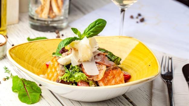 Insalata caesar con salmone. mix di insalate, pomodorini, parmigiano, basilico.