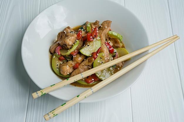 Insalata calda con pollo, zucchine e peperoncino, cosparsa di semi di sesamo ed erbe. cibo asiatico. legno bianco .